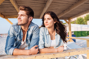 Young tender beautiful couple looking at the sea while standing at the wooden beach house