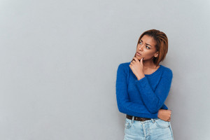 Young thoughtful african woman in sweater looking aside and holding one hand to the chin. Isolated gray background