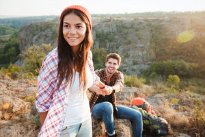 Young traveler couple in the mountains. girl holding man. man on background