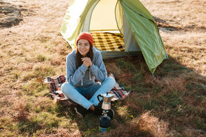 Young traveler woman sitting outdoors in the morning near a tent