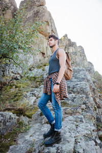 Young traveling man with backpack stands sideways on rock. full length image