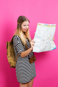 Young traveling woman holding a map on a pink background