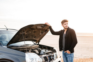 Young upset casual man standing at his broken car outdoors