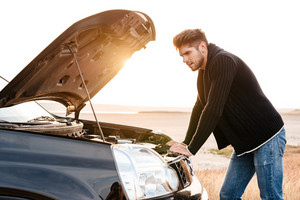 Young upset casual man trying to fix his broken car outdoors
