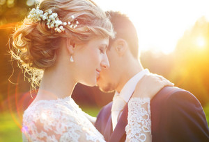 Young wedding couple enjoying romantic moments outside on a summer meadow