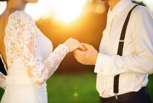 Young wedding couple holding hands as they enjoy romantic moments outside on a summer meadow