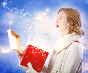 Young woman amazed upon opening a magical Christmas present