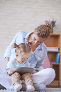 Young woman and her cute daughter browsing online at leisure