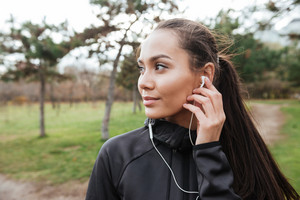 Young woman attractive runner in warm clothes and earphones in autumn park. Look aside.