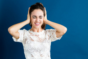 Young woman blocking her ears on a dark blue back ground