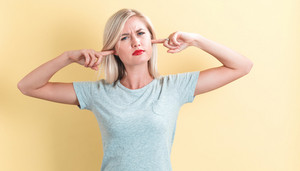 Young woman blocking her ears on a yellow background