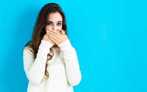 Young woman covering her mouth on a blue background