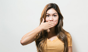 Young woman covering her mouth on a off white background