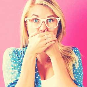 Young woman covering her mouth on a pink background