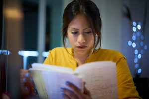Young woman doing homework at night. Tired hispanic girl and college education. Female student studying for next day exam