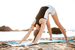 Young woman doing yoga exercises on yoga mat on beach in the morning