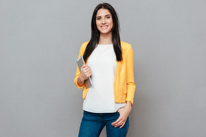 Young woman dressed in yellow jacket holding tablet computer over grey background. Look at camera.