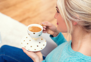 Young woman drinking a cup of coffee at home