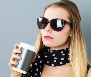Young woman drinking coffee on a gray background