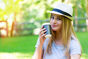 Young woman drinking coffee outside on a summer day