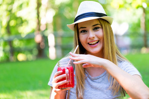 Young woman drinking smoothie outside on a summer day