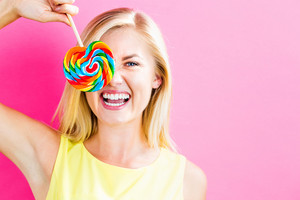 Young woman eating a lollipop on a pink background
