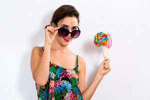 Young woman eating a lollipop on a white background