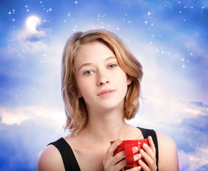 Young woman enjoying a cup of coffee at night