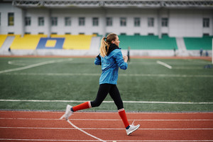 Young woman exercise jogging and running on athletic track on stadium