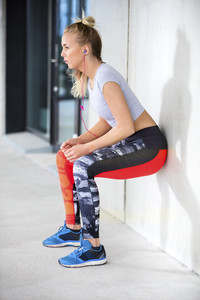 Young Woman Exercising Muscle Strength Against Wall
