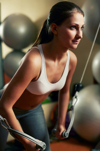 Young woman exercising with plate load machine