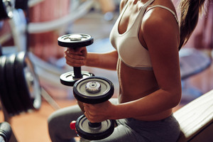 Young woman exercising with weights
