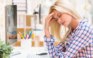 Young woman feeling stressed at her desk