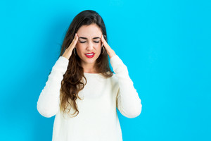Young woman feeling stressed on a blue background