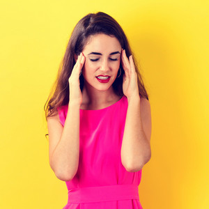 Young woman feeling stressed on a yellow background