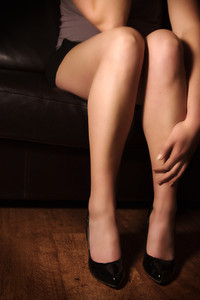 Young woman / girl sitting lonely on a leather couch. Holding her hand at her leg.