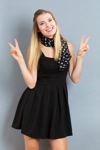 Young woman giving the peace sign on a gray background