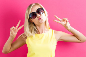 Young woman giving the peace sign on a pink background