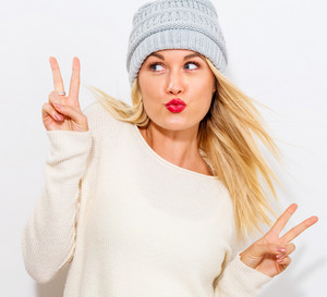 Young woman giving the peace sign on a white background