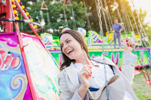 Young woman having fun at fun fair, chain swing ride, amusement park