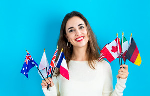 Young woman holding a collection of international flags