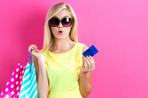 Young woman holding a credit card and shopping bags