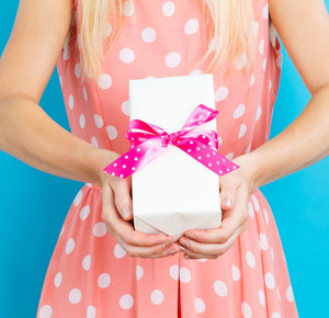 Young woman holding a gift box on a blue background