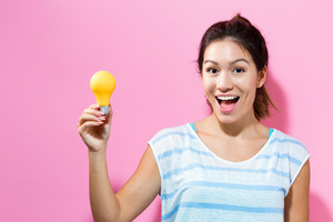 Young woman holding a light bulb on a pink background