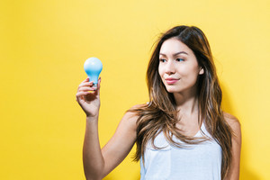 Young woman holding a light bulb on a yellow background