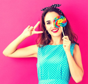Young woman holding a lollipop on a pink background