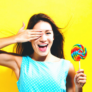 Young woman holding a lollipop on a yellow background