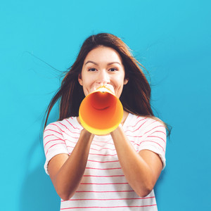 Young woman holding a paper megaphone on a blue background