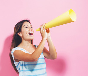 Young woman holding a paper megaphone on a pink background