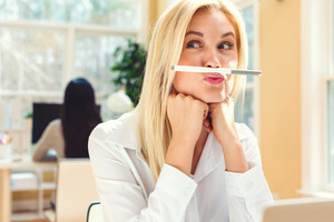 Young woman holding a pen above lips in an office